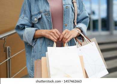 Young girl in denim jacket holding various bags with new clothes while standing outside mall