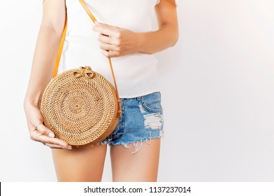 Young girl in denim shorts and a white sweatshirt with a trendy stylish rattan bag against the backdrop of a light wall. Rattan handbag, ecobags from Bali. Eco-bag concept, trendy bamboo bag. Copy