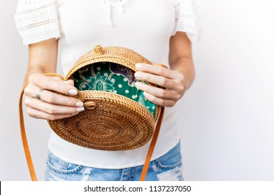 Young girl in denim shorts and a white jacket opens a stylish natural rattan bag against the backdrop of a light wall. Rattan handbag, ecobags from Bali. Eco-bag concept, trendy bamboo bag. Copy space