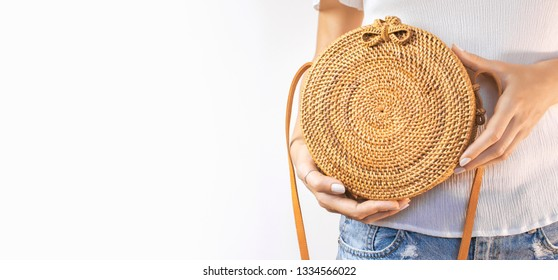 Young girl in denim shorts and a white sweatshirt with a trendy stylish rattan bag against the backdrop of a light wall. Rattan handbag ecobags from Bali. Eco-bag concept trendy bamboo bag. Copy space