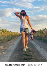 Young girl in denim shorts and white T-shirt is walking along rural road. View from back.