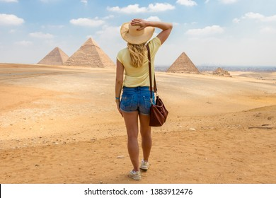 Young girl in the desert. Back view portrait of a single woman watching the Great Pyramids of Giza in Egypt