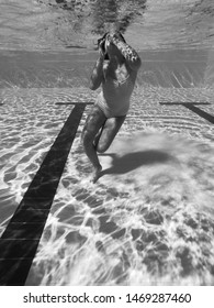 Young girl dives into a pool in a summer day. Underwater view