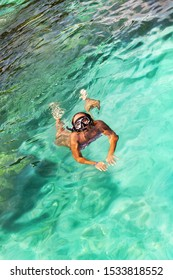 Young girl with diving mask and snorkel dives in clear blue sea water, adult woman in white bikini swims in turquoise clean transparent ocean water, tropical coral reef snorkeling on summer holidays