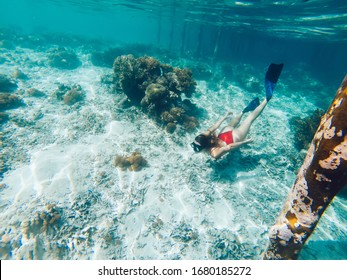 Young girl with diving mask and snorkel flippers in clear blue sea water, woman in red bikini swims in turquoise crystal transparent ocean water, tropical coral reef snorkeling on summer holidays