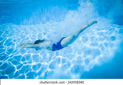 young girl diving in the swimming pool