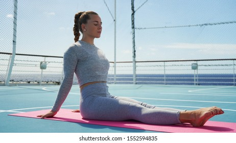 young girl do yoga in gray suit on a light background. Dramatic sky. Blonde girl yoga asana on a background of blue sky with clouds.