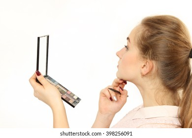 young girl does a makeup in front of a small cosmetic mirror. white background