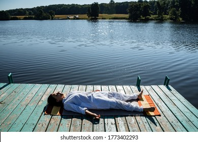 a young girl does yoga on a lake on a Sunny summer day, meditation, relaxation pose, Shavasana or dead man's pose, retreat in nature, peace, relaxation
