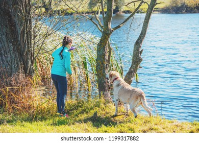 Young girl with dog on the lake shore in autumn. Girl holding in the hand a ring for traning throwing it in water
