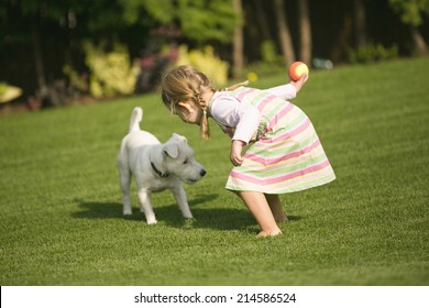 Young girl with dog playing in garden