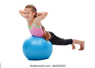 Young girl doing back strengthening gymnastic exercises with a smile, using a large rubber ball - isolated