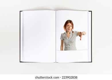 Young girl doing a bad signal printed on book