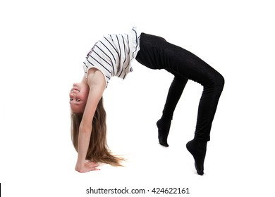 A young girl is doing bridge pose in studio
