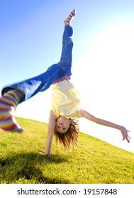Young girl doing cartwheel across green grass