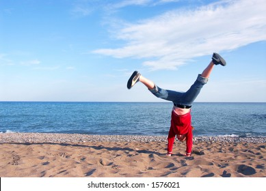 Young girl doing cartwheel on a beach