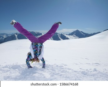 Young girl doing cartwheel in snow