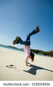 Young girl doing cartwheels on a beach.