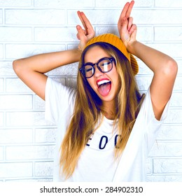 Young girl doing emotion, hands raised up in the form of rabbit ears . Dressed in a white shirt, yellow hat, glasses and bright lips, trendy clothes.