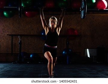 Young girl doing exercise in the gym, high contrast low key, dark image