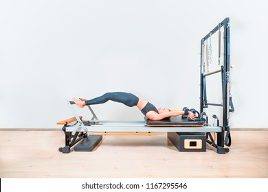Young girl doing exercise of pilates, reformer bed with instructor