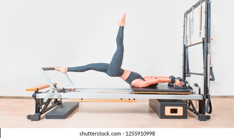 Young girl doing exercise of pilates, reformer bed