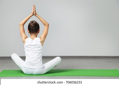 Young girl doing exercises on green yoga mat
