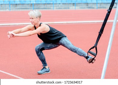 young girl doing exercises outdoors using slings, TRX loop