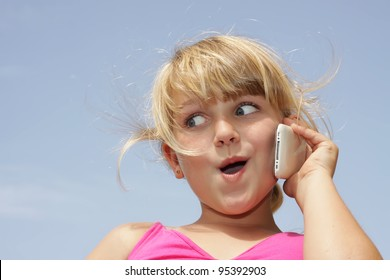 A young girl is doing a funny face while talking on her smart phone