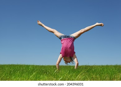 Young girl doing a handstand in a meadow