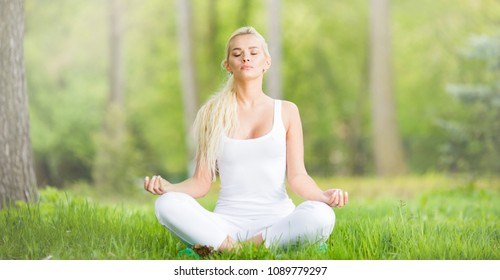 Young girl doing lotus yoga exercise in spring park