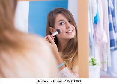 Young girl doing makeup in front of mirror.