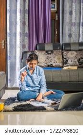 若い女の子は、ノートパソコンを使って、床に座ってオンラインで自習をしている