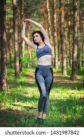 Young girl doing physical exercises in the park in a forest area.