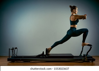 Young girl doing pilates exercises with a reformer bed. Beautiful slim fitness trainer on a reformer gray background, low key, art light, copy space advertising banner