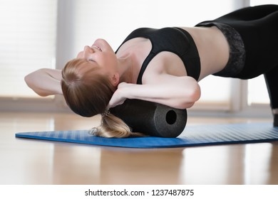 Young girl doing sport excercise with fascia roll