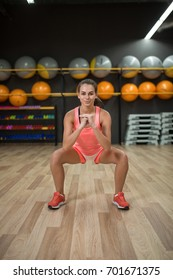 A young girl doing squats on a colorful gym background. A marvelous woman with perfect body doing exercises in a gym.