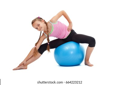 Young girl doing stretching gymnastic exercises sitting on a large rubber ball - isolated