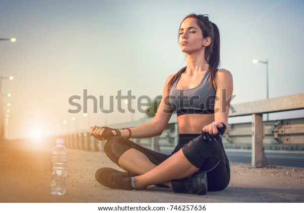 Young girl doing yoga in early morning outdoors.