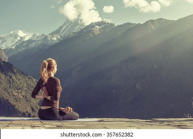 Young girl doing yoga fitness exercise outdoor in beautiful mountains landscape. Morning sunrise, Namaste Lotus pose. Meditation and Relax