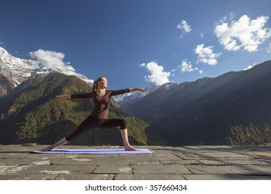 Young girl doing yoga fitness exercise outdoor in beautiful mountains landscape. Morning sunrise, Warrior Pose
