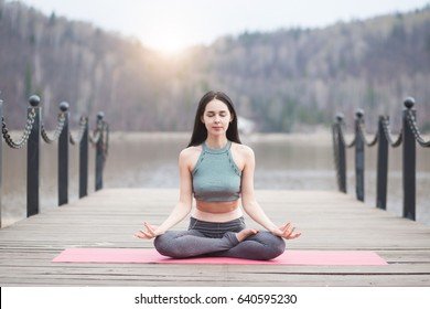 Young girl doing yoga or fitness exercise outdoor in nature with beautiful lake and mountains landscape at morning sunrise, Namaste pose. Meditation and Relax concept