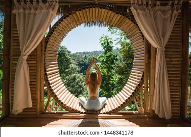 Young girl doing yoga outdoor. Young woman practicing yoga in bamboo house, nature on background.Female happiness.Caucasian woman practicing yoga on vacation on Bali island