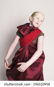 A young girl in draped fabric striking a pose.