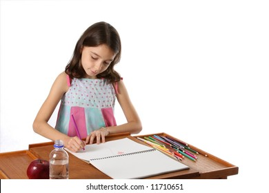 young girl drawing in book at desk with apple and water bottle