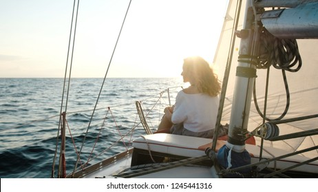 Young girl in a dress sits on the deck of a sailing yacht near the mast