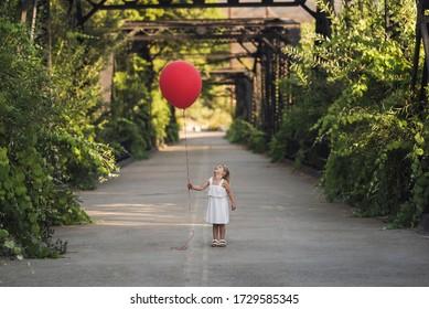 Young girl dress standing on Steele Canyon Bridge with big red balloon