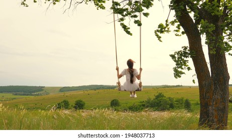 A young girl in dress swinging on swing in evening park. Wooden swing with swinging free, happy woman outdoors. Swing on a swing, dreams of flying. Travel in spring summer in nature. Healthy lifestyle