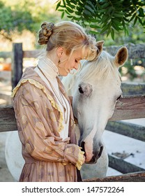 Young Girl dressed in 1800s Vintage Clothing petting horse