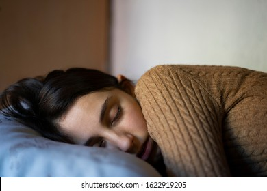Young girl dressed in brown napping. Nap and sleep concept.